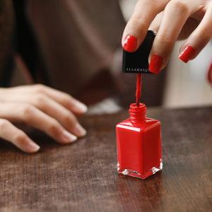 Red nail polish in application